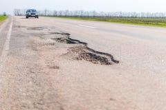 Grote diepe pothole een voorbeeld van slechte weg stock foto