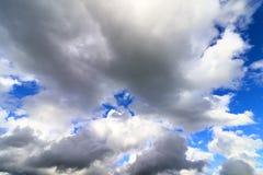 Grote dikke witte en donkere wolken in de blauwe hemel Stock Fotografie