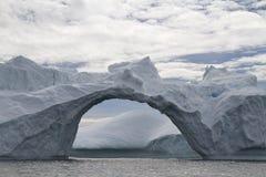 Grote door-boog in een ijsberg op bewolkt Royalty-vrije Stock Afbeeldingen