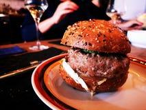 Grote eigengemaakte hamburger op plaat met vrouw op de achtergrond royalty-vrije stock afbeelding