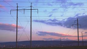 Grote elektropylonen die tot de stad op de zonsonderganghemel leiden stock videobeelden