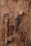Grote en kleine roestige uitstekende metaalsleutels op oude houten backgroun stock fotografie