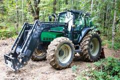 Grote en moderne die tractor in het bos wordt geparkeerd stock foto's