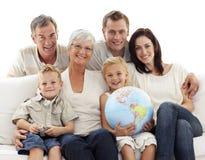 Grote familie die op bank een aardse bol houdt Stock Afbeeldingen