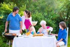 Grote familie die vlees voor lunch met grootmoeder roosteren stock afbeeldingen