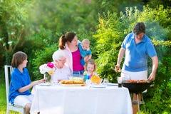 Grote familie die vlees voor lunch roosteren royalty-vrije stock afbeeldingen
