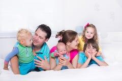 Grote familie met jonge geitjes in bed royalty-vrije stock foto's