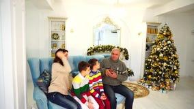 Grote familie op laag babbelen, vrouw op telefoon met binnen verwanten en handenbuis die aan man zitting op blauwe bank spreken stock video