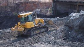 Grote gele bulldozer die dichtbij de fabriek werken stock videobeelden