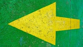Grote gele pijl die aan de linkerzijde met groene achtergrond richten Stock Afbeelding