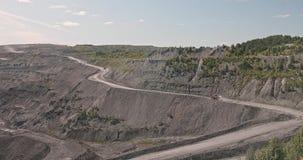 Grote gele zware vrachtwagen in open - gegoten mijnmijnbouw van steenkool het algemene plan Open kuil antraciet mijnbouw, mijnbou stock videobeelden