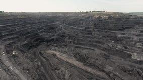Grote gele zware vrachtwagen in open - gegoten mijnmijnbouw van steenkool het algemene plan Open kuil antraciet mijnbouw, mijnbou stock video