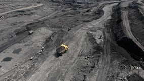 Grote gele zware vrachtwagen in open - gegoten mijnmijnbouw van steenkool het algemene plan Open kuil antraciet mijnbouw, mijnbou stock footage