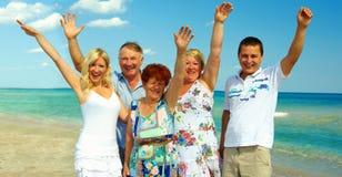 Grote gelukkige familie golvende handen op overzees strand Stock Foto