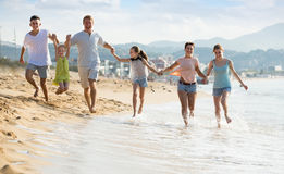 Grote glimlachende familie van zes mensen die gelukkig lopen Stock Afbeeldingen