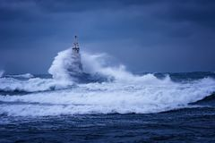 Grote golf tegen oude Vuurtoren in de haven van Ahtopol, de Zwarte Zee, Bulgarije op een humeurige stormachtige dag Gevaar, drama stock afbeeldingen
