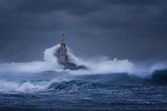 Grote golf tegen oude Vuurtoren in de haven van Ahtopol, de Zwarte Zee, Bulgarije op een humeurige stormachtige dag Gevaar, drama royalty-vrije stock afbeeldingen