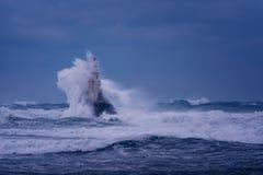 Grote golf tegen oude Vuurtoren in de haven van Ahtopol, de Zwarte Zee, Bulgarije op een humeurige stormachtige dag Gevaar, drama royalty-vrije stock foto