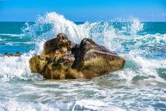 Grote golfneerstorting tegen de rotsen bij het strand Stock Afbeeldingen