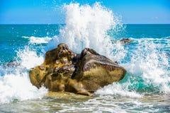 Grote golfneerstorting tegen de rotsen bij het strand Royalty-vrije Stock Afbeeldingen