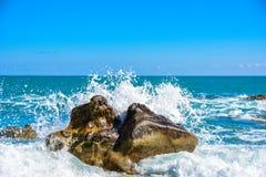 Grote golfneerstorting tegen de rotsen bij het strand Stock Fotografie