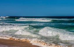 Grote golven die binnen aan het strand van een turkooise overzees onder een blauwe hemel rollen Stock Foto