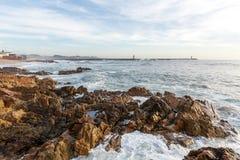 Grote golven die en op de rotsen breken bespatten stock afbeelding