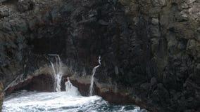 Grote golven die op klip van lavarotsen verpletteren stock videobeelden
