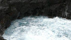 Grote golven die op klip van lavarotsen verpletteren Langzame Motie stock video