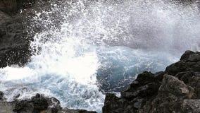 Grote golven die op klip van lavarotsen verpletteren Langzame Motie stock footage
