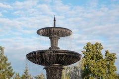 Grote granietfontein in een stadspark op een achtergrond van een heldere blauwe hemel Stock Afbeelding