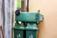 Grote groene die wheeliebak niet in gebruik wordt gestapeld stock afbeeldingen