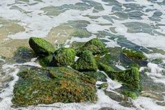 Grote groene stenen in zeewater en golven in wit schuim royalty-vrije stock afbeelding