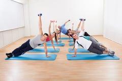 Grote groep die mensen in een gymnastiek uitwerken Stock Afbeelding
