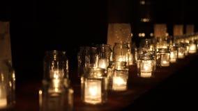 Grote groep glaskruiken met het branden van kaarsen stock videobeelden
