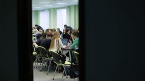 Grote groep mensen in een grote lichte klaslokaalzitting bij het bureau en het samenwerken De jonge economen zitten bij