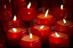Grote groep rode kaarsen die in dark glanzen Royalty-vrije Stock Afbeelding