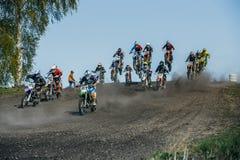 Grote groep ruiters op motorfietsen die over een berg springen Royalty-vrije Stock Foto