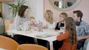 Grote groep vrienden en hun kinderen die weekenddag in een koffie doorbrengen, familiekoffie stock footage
