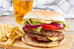 Grote hamburger met frieten en bier stock foto