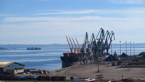 Grote havenkranen die lading laden bij een schip Stock Afbeelding