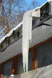Grote ijskegel op een de bouwdak Stock Afbeelding