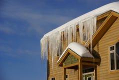 Grote ijskegels op Huizen in de stad na zware sneeuwstorm Stock Foto's