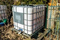 Grote industriële vloeibare tank met een capaciteit van 1000 liter, 265 gallons met een metaal beschermend traliewerk Geplaatst i royalty-vrije stock afbeeldingen
