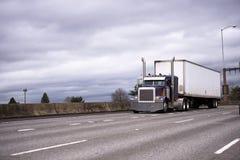 Grote installatie donkerblauwe klassieke semi vrachtwagen met droge bestelwagen semi aanhangwagen r stock fotografie