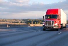 Grote installatie rode semi vrachtwagen die zich met aanhangwagen op brede weg bewegen Stock Afbeelding