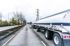 Grote installatie semi vrachtwagen die brandstof in twee tank semi aanhangwagens vervoeren die op rechte verdeelde weg drijven royalty-vrije stock foto's