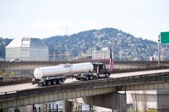 Grote installatie zwarte semi vrachtwagen die brandstof in lange tank semi tra vervoeren Stock Fotografie