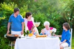 Grote jonge familie die vlees voor lunch met grootmoeder roosteren royalty-vrije stock fotografie