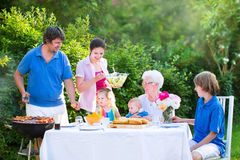 Grote jonge familie die vlees voor lunch op zonnige dag roosteren royalty-vrije stock afbeeldingen
